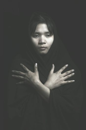 Young woman wearing scarf gesturing standing against black background