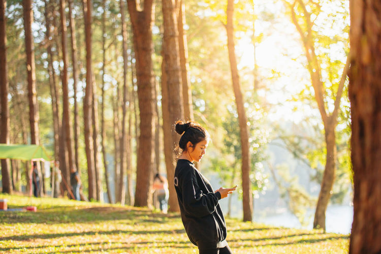 Side view of woman using mobile phone while standing in forest