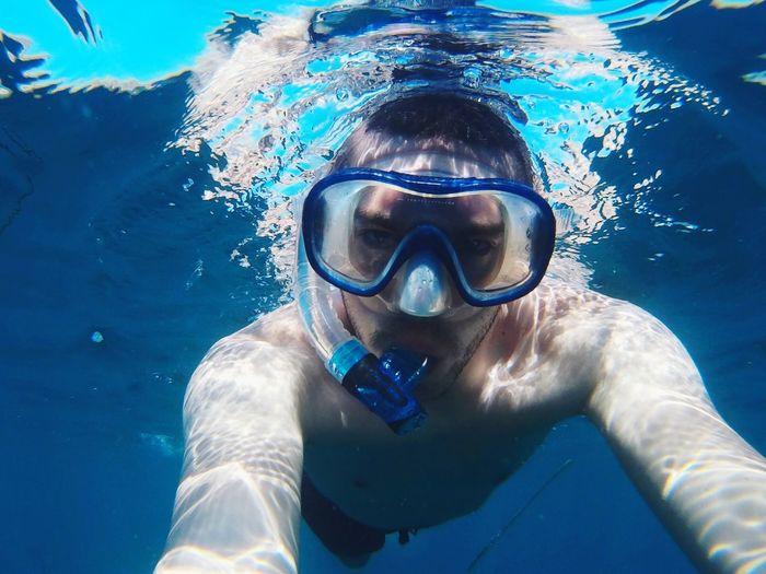 Portrait of shirtless man wearing snorkel swimming undersea