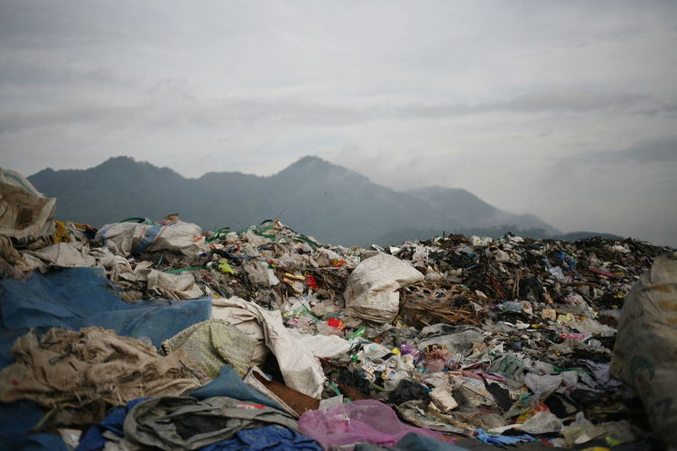 Stack of garbage on mountain range against sky