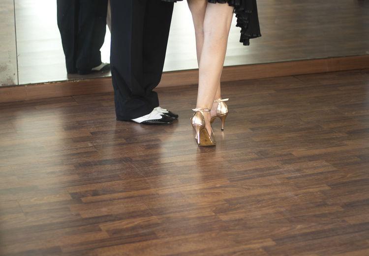 Low section of people standing on hardwood floor