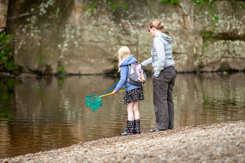 Side view of mother and daughter fishing in lake with nets