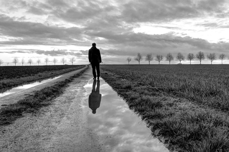Rear view of man on pathway amidst field against cloudy sky