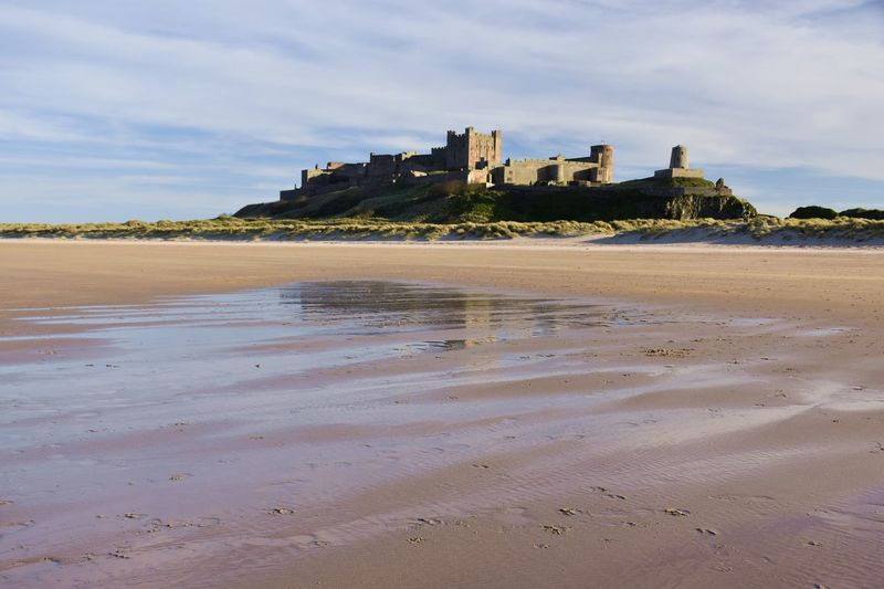 Looking up at Bamburgh Castle from the beach Water Built Structure Architecture Land Sky Building Exterior Beach Sand Sea Nature Building Cloud - Sky Castle History The Past Day No People Outdoors Bamburgh Bamburgh Castle Castle Castle View  Historic Historical Building Sandy Beach Reflection Reflections Blue Sky Sunlight Backgrounds Scenics Coastline Coast Coastal Feature Background View Dunes Evening Evening Light The Traveler - 2019 EyeEm Awards