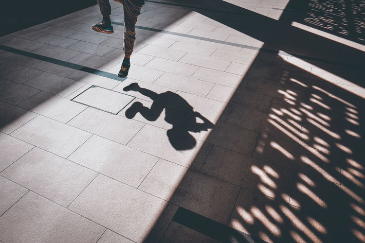 Happiness Sunlight Focus On Shadow Footpath High Angle View Human Leg Jumping Leisure Activity Lifestyles Light And Shadow Low Section Paving Stone Plaza Shadow Street Sunlight Walking A New Perspective On Life Capture Tomorrow