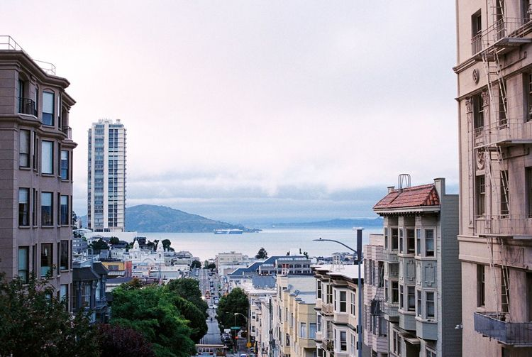 High Angle View Of Buildings By Sea Against Sky