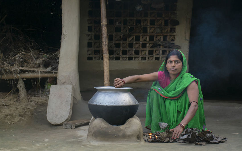 Woman making food on traditional chulha or firewood