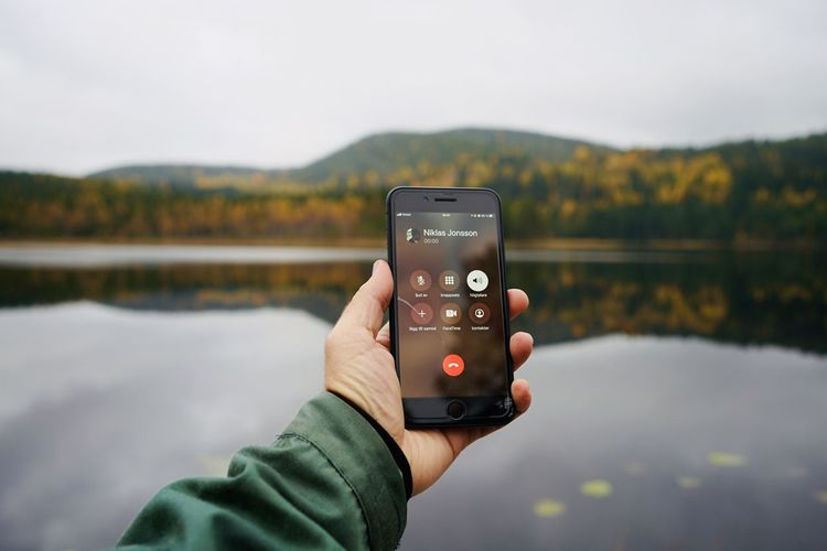 Man photographing with mobile phone in lake