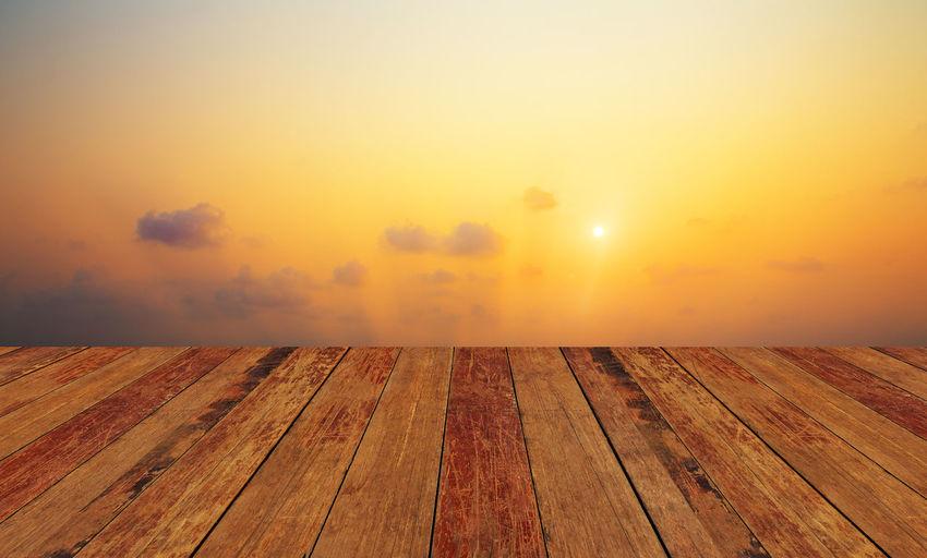 Wooden floor against sky during sunset