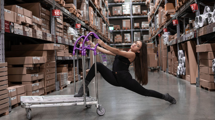 Side view of woman with arms raised and push cart dancing on floor in warehouse