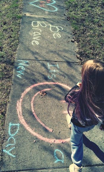 High angle view of girl playing hopscotch outdoors