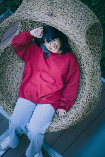 High angle portrait of girl sitting in hanging chair