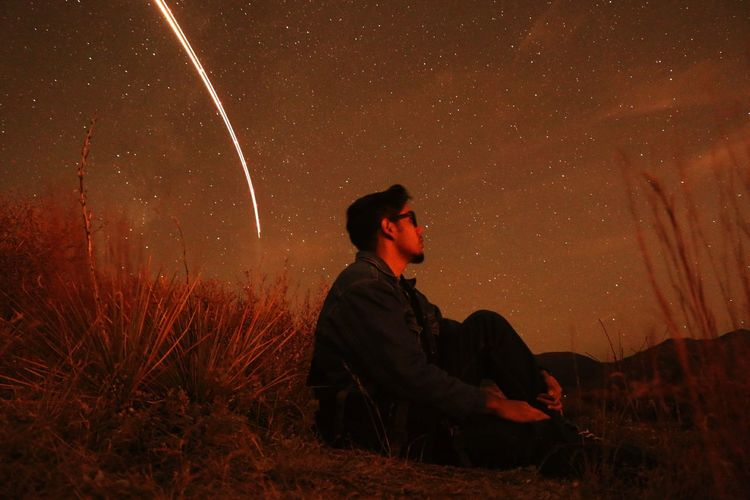 Side view of man sitting against sky at night