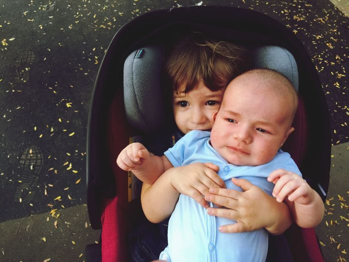 Close-Up Of Siblings In Baby Carriage