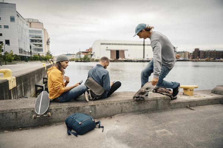 Men sitting in city against sky