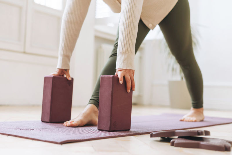 Attractive middle aged woman in sportswear ptactice yoga with equipment in light studio