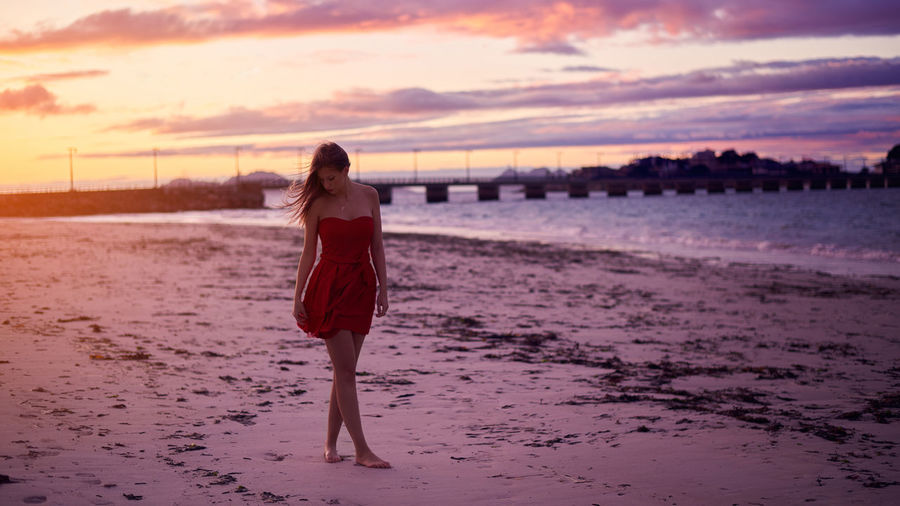 Woman looking down while standing on beach against sky during sunset