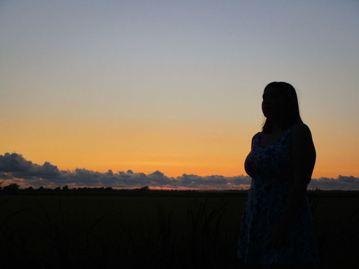 Silhouette teenage girl standing on field against sky during sunset