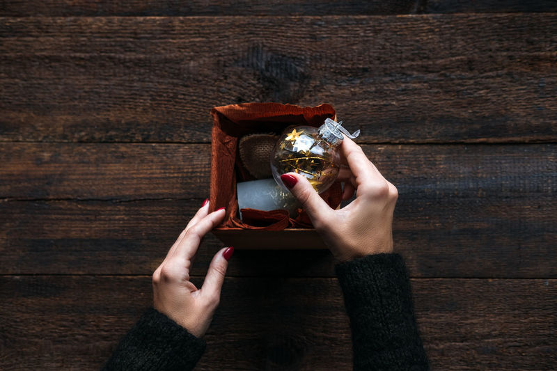 High angle view of woman holding ice cream on wooden table