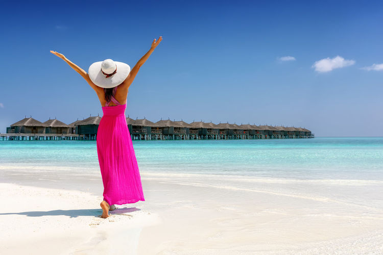 Hapyp woman in a pink summer dress enjoys her vacation time on a tropical beach in the Maldives islands One Person Water Lifestyles Clothing Beach Sea Trip Holiday Real People Arms Raised Fashion Women Standing Outdoors Leisure Activity Vacations Traveler Travel Maldives Summer Dress Tourist Island Tropical Climate Happiness