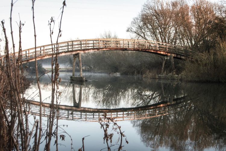 Water Bare Tree Tree Winter Nature Cold Temperature No People Sky Outdoors Snow Beauty In Nature Day Built Structure Footbridge Tranquility River Bridge - Man Made Structure Britain Beauty In Nature