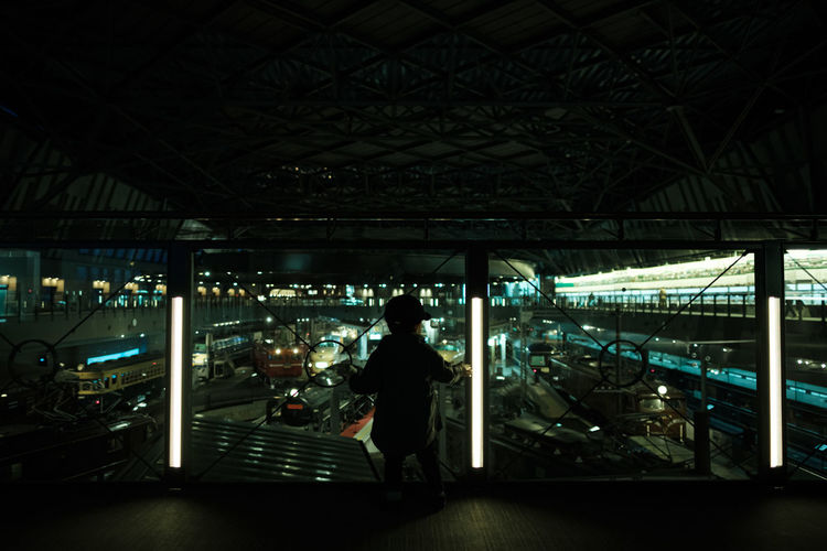 Rear view of man standing at illuminated station