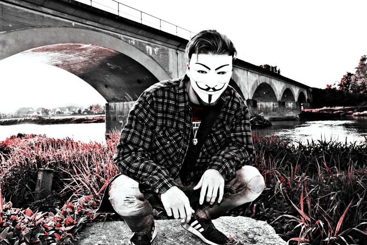 Man sitting by bridge