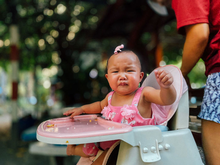Portrait of cute baby girl crying while sitting on high chair in yard