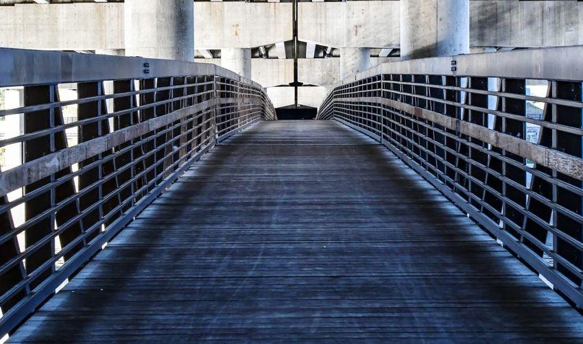 Empty footpath under bridge