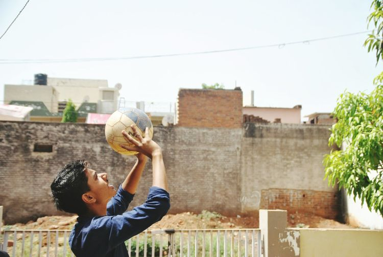 Side view of man holding basketball against building