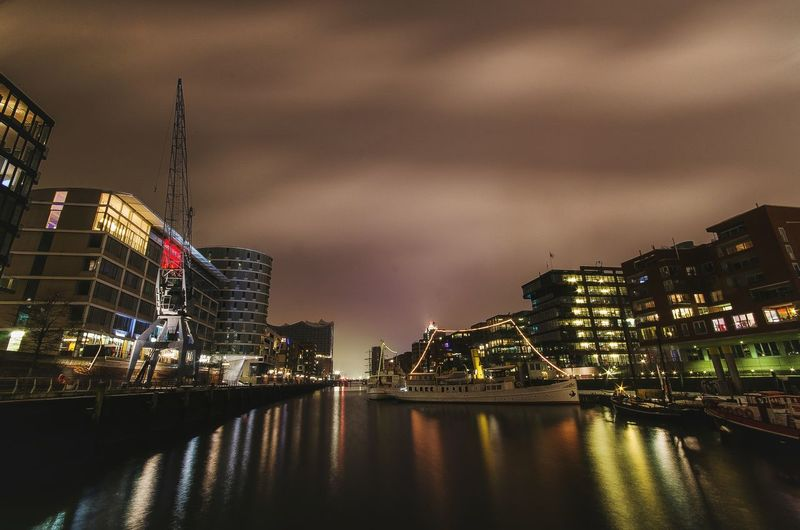 Illuminated buildings by canal against sky in city