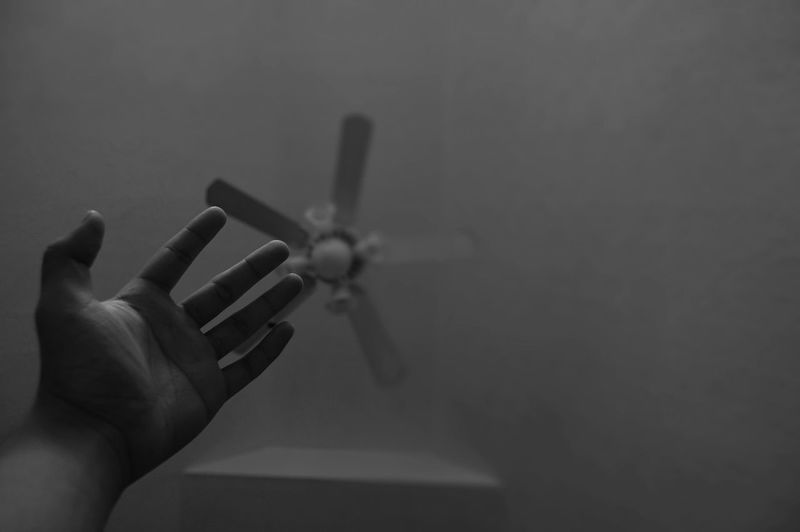 Cropped hand against ceiling fan at home