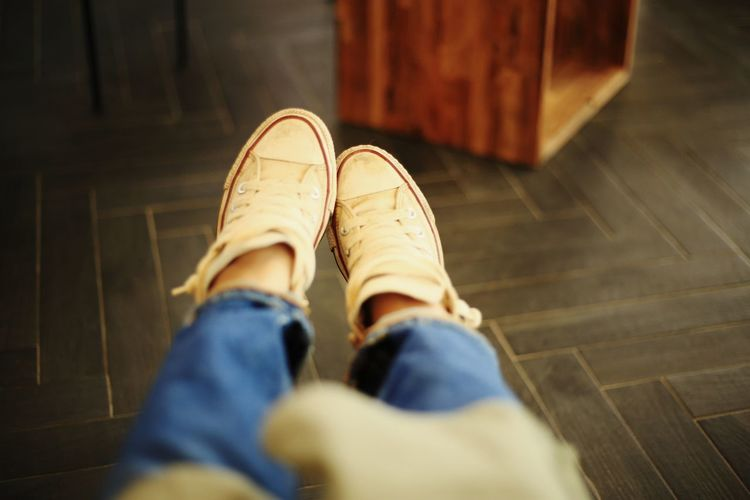 Low section of person wearing shoes at home