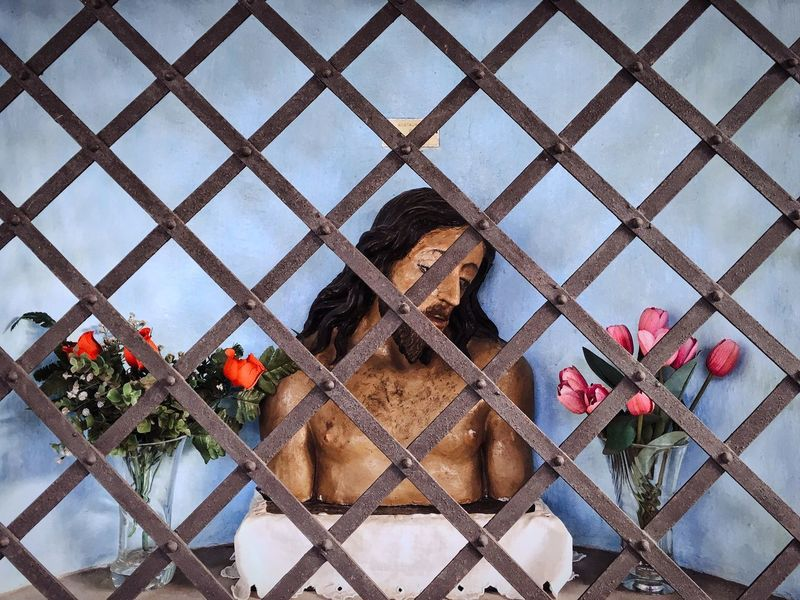 A caged Jesus amidst some flowers. He looks so unhappy. Cage Flower Grate Grated Grid Imprisoned Jesus No People On Display Painted Rusty Statue Suffering Torso Wood Wood - Material