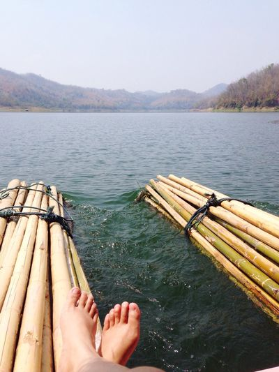 Low section of woman resting on raft over river
