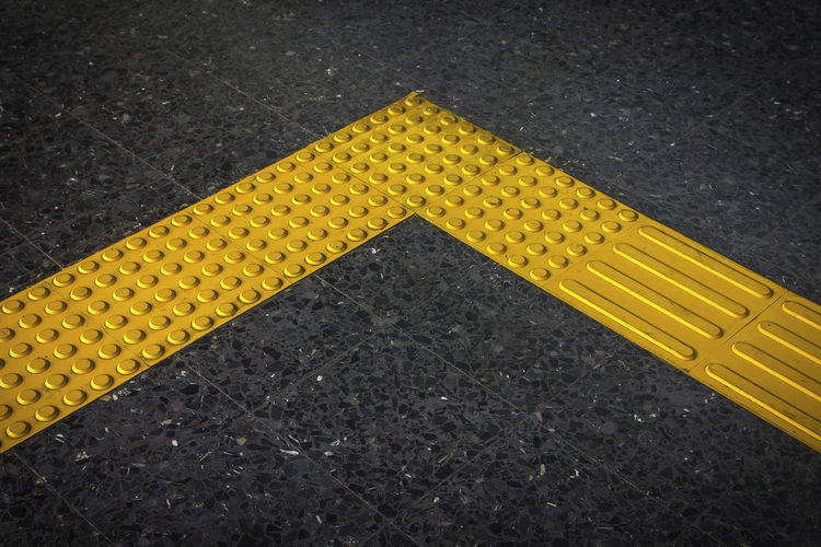 High angle view of yellow sign on road