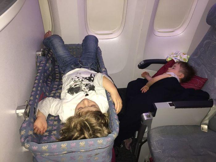 Siblings sleeping in airplane