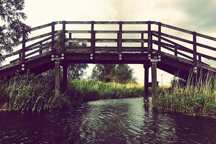 Bridge - Man Made Structure Built Structure Connection Outdoors Architecture Water Day River Sky No People Footbridge Cloud - Sky Plant Nature Grass Tree