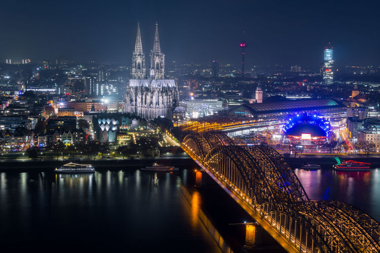 View of the illuminated City of Cologne, the Cologne Cathedral, the Hohenzollernbridge and the River Rhine at Night - in Germany Cologne 2018. Cologne Cathedral Church City Germany Cologne Night Rhine River Hohenzollernbridge Bridge Tourist Destination Tourism Travel Illuminated Reflection Long Exposure Water Urban Europe Travel Destinations Architecture Building Exterior Skyscraper Connection Building No People Bridge - Man Made Structure Built Structure Sky Cityscape