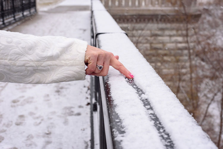 Cropped hand of woman making line in snow on railing