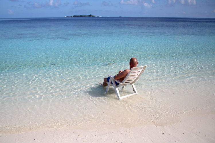 Man sitting on chair at beach