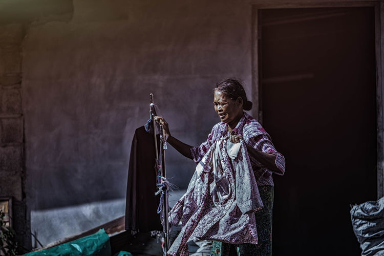 Senior woman holding clothes
