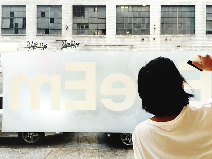 Rear view of man working on advertising banner