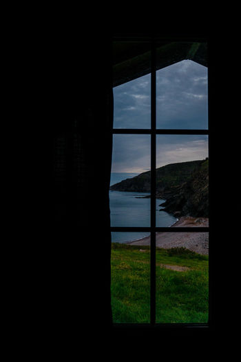 Looking through a window at the coastline in Meat Cove, Nova Scotia, Canada. Cape Breton Island Nova Scotia, Canada Atlantic Coast Beauty In Nature Cloud - Sky Coastal Feature Coastal Landscape Day Glass - Material Horizon Horizon Over Water Indoors  Land Meat Cove Morning View Sky And Sea Nature No People Scenics - Nature Sea Sky Tranquil Scene Tranquility Water Window Window Frame