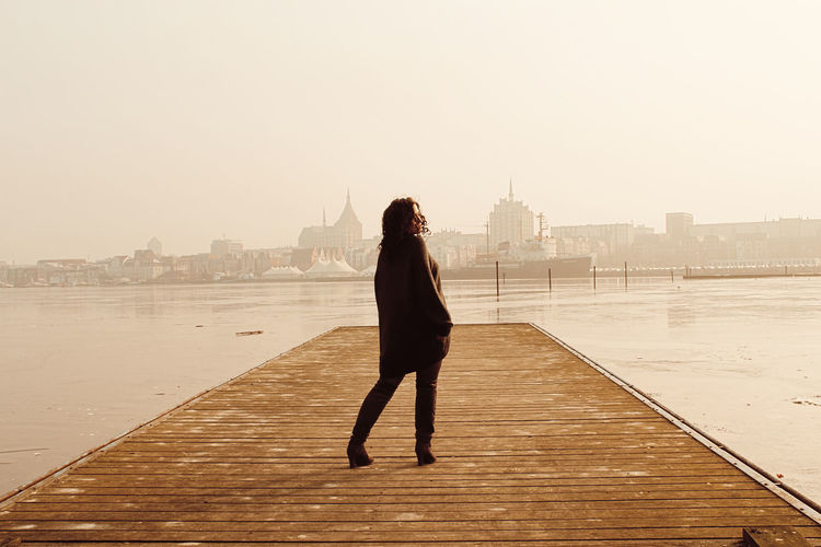 Full length rear view of woman standing on pier over lake against clear sky