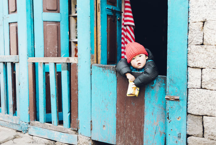 Friendly locals! Doors The Week on EyeEm Blue Child Childhood Clothing Cute Day Door Entrance Friendly House Innocence Knit Hat Leisure Activity Lifestyles Males  One Person Outdoors Portrait Real People Warm Clothing Winter Wood - Material