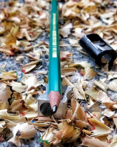 Close-up of pencil with sharpener and shavings on table