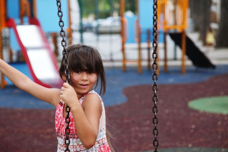 Portrait of smiling girl standing by swing at playground