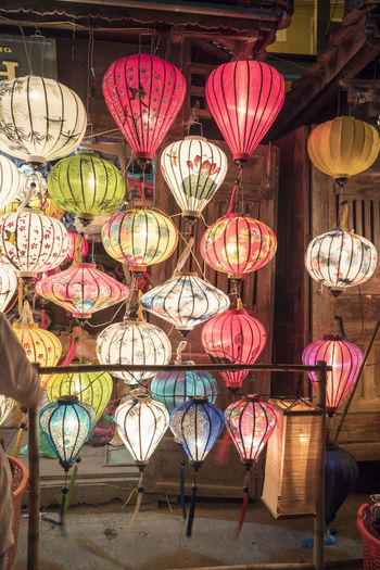 Illuminated lanterns hanging at market stall