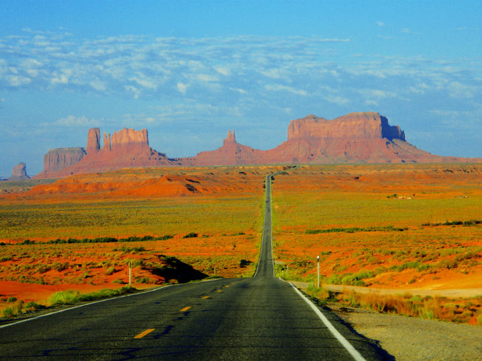 Road leading towards rocky mountains against sky at monument valley